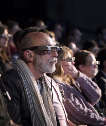 een rij mensen met ondertitelingsbril op