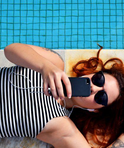foto van een meisje bij een zwembad met oordopjes in