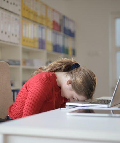 Een vrouw legt haar hoofd op haar laptop