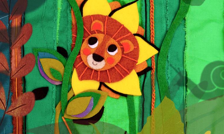 Leeuw in het gras uit voorstelling De Wondertuin