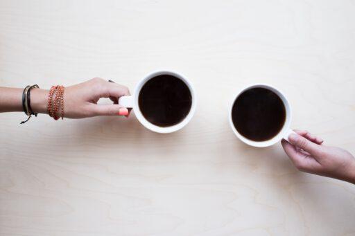 twee handen die een kop koffie vasthouden